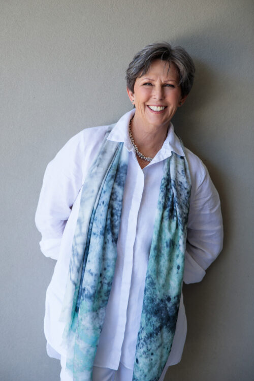 Career coach Therese Toohey looking resplendent in white shirt and silk scarf. Leaning casually against the wall following a coaching session.